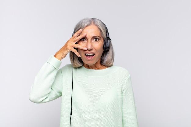 Женщина среднего возраста выглядит потрясенной, напуганной или напуганной, закрывает лицо рукой и смотрит между пальцами. музыкальная концепция