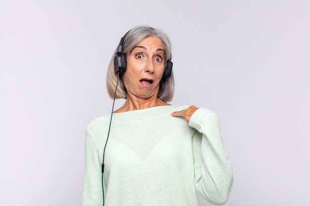 Middle age woman looking shocked and surprised with mouth wide open, pointing to self. music concept