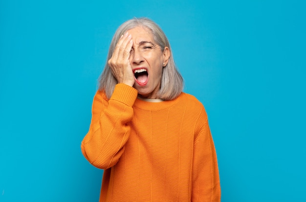 Middle age woman looking sleepy, bored and yawning, with a headache and one hand covering half the face