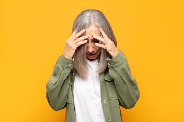 스트레스와 좌절감을 느끼는 중년 여성, 두통으로 압력을 받고 문제로 어려움을 겪고 있습니다.