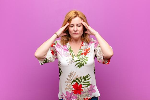 ストレスと欲求不満を見ている中年の女性、頭痛のプレッシャーの下で働いていて問題に悩んでいる