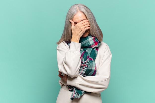 스트레스, 부끄러움 또는 화가 난 중년 여성, 두통, 손으로 얼굴 덮음