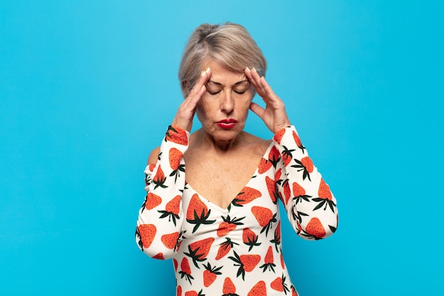 Middle age woman looking stressed and frustrated, working under pressure with a headache and troubled with problems