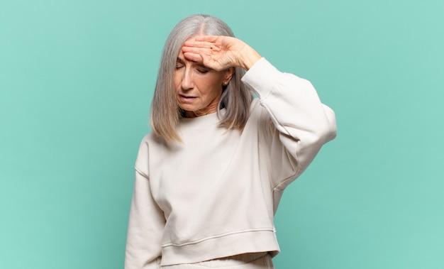중년 여성이 스트레스를 받고 피곤하고 좌절감을 느끼고 이마에서 땀을 말리고 절망적이고 지친 느낌