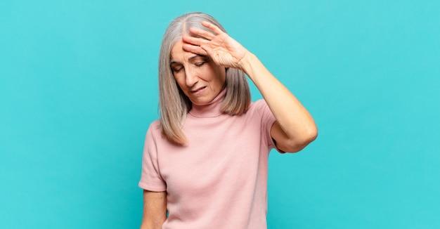 ストレス、疲れ、欲求不満を感じ、額から汗を乾かし、絶望的で疲れ果てている中年女性