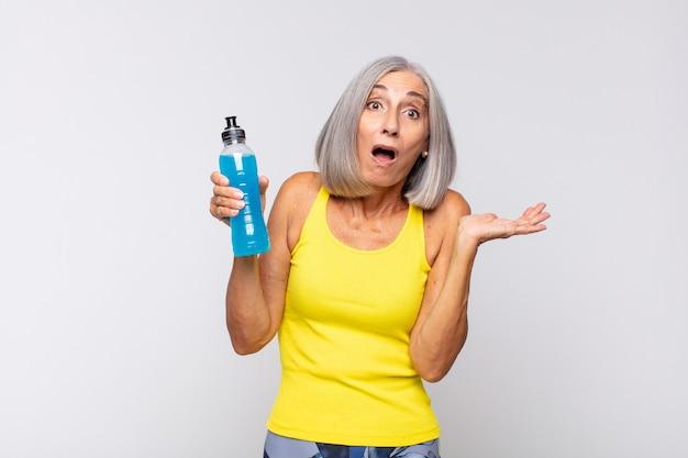 Женщина среднего возраста, выглядящая удивленной и шокированной, с отвисшей челюстью, держащей объект открытой рукой по бокам. фитнес-концепция