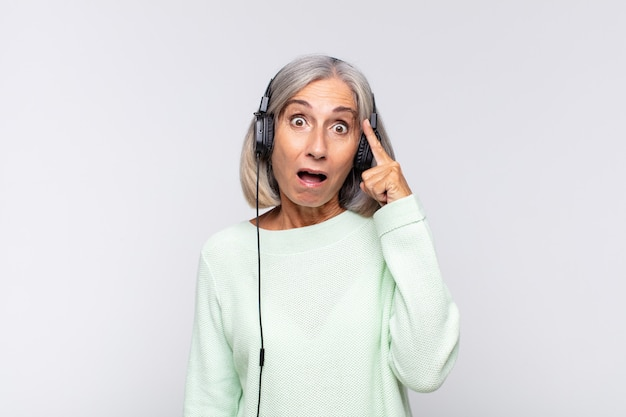 Женщина среднего возраста выглядит удивленной, с открытым ртом, шокированной, осознающей новую мысль, идею или концепцию. музыкальная концепция