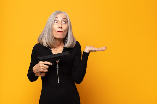 Middle age woman looking surprised and shocked, with jaw dropped holding an object with an open hand on the side