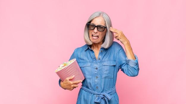 불행하고 스트레스를 받는 중년 여성, 손으로 총기 표시를 하는 자살 제스처, 머리 영화 개념을 가리키는