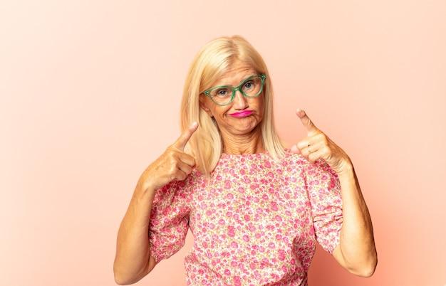 Женщина среднего возраста выглядит несчастной и подчеркнутой, жест самоубийства делает знак пистолета рукой, указывая на голову