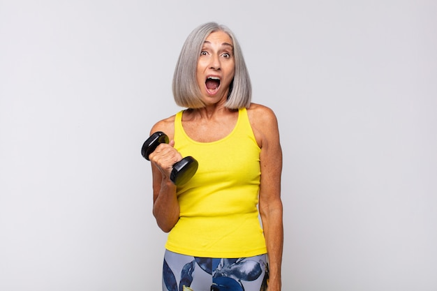 Middle age woman looking very shocked or surprised, staring with open mouth