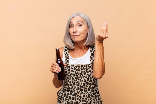 Женщина среднего возраста делает капризный или денежный жест, говоря вам, чтобы вы заплатили свои долги! с пивом