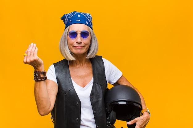 Женщина среднего возраста делает капризный или денежный жест, говоря вам, чтобы вы заплатили свои долги!