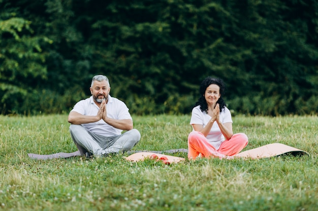 Middle age woman and man  doing yoga together outdoors making gesture namaste.