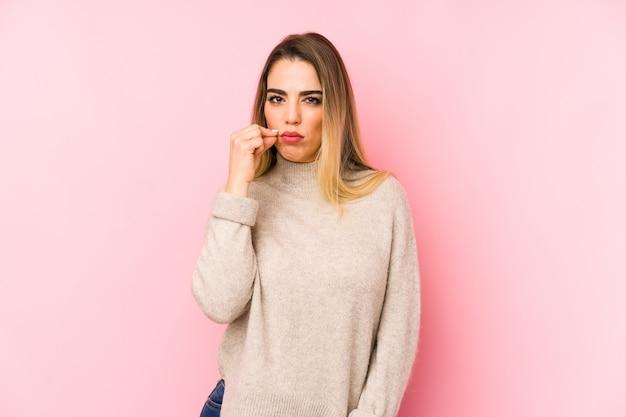 비밀을 유지하는 입술에 손가락으로 격리 된 배경 위에 중 년 여자.