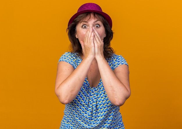 Middle age woman in party hat  being shocked covering mouth with hands celebrating birthday party standing over orange wall