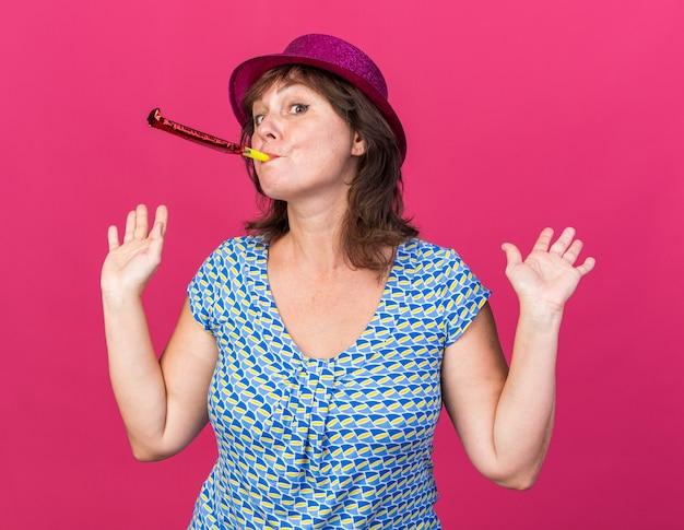 Donna di mezza età in cappello da festa che soffia nel fischietto guardando confusa alzando le braccia che celebra la festa di compleanno in piedi sul muro rosa pink