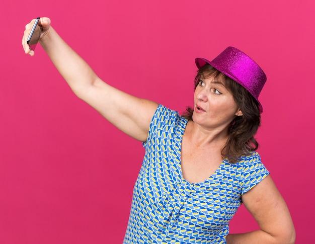 Donna di mezza età in cappello da festa che fa selfie utilizzando smartphone sorridente felice e allegro