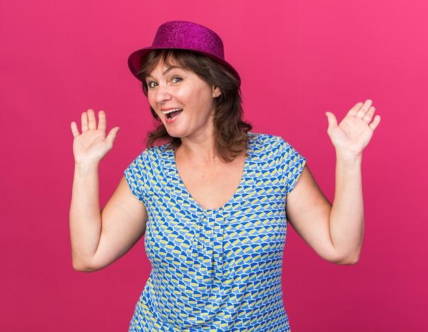 Donna di mezza età in cappello da festa felice ed eccitata che alza le braccia