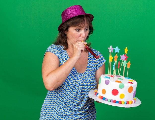 Middle age woman in party hat holding birthday cake blowing whistle happy and surprised celebrating birthday party standing over green wall