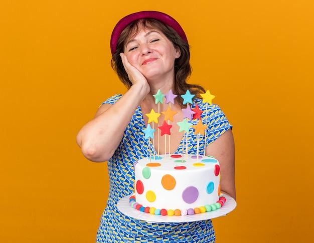 Donna di mezza età con cappello da festa che tiene in mano una torta di compleanno felice e positiva che sorride allegramente