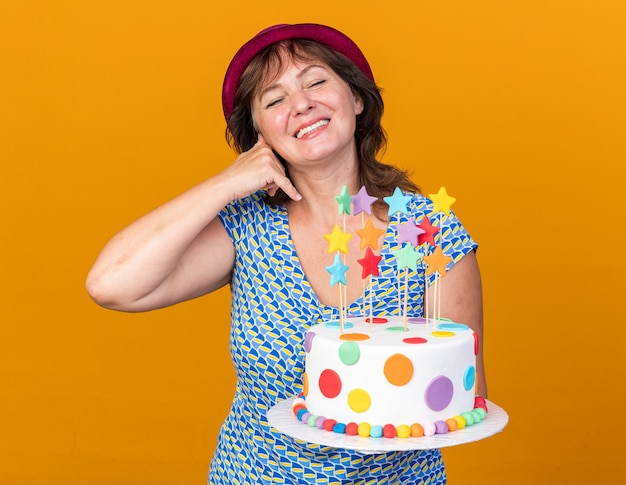 Middle age woman in party hat holding birthday cake smiling cheerfully happy and positive making call me gesture celebrating birthday party standing over orange wall