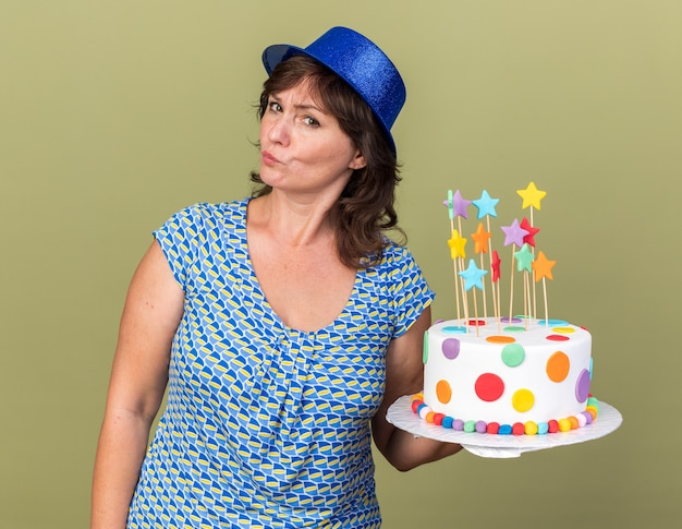 Middle age woman in party hat holding birthday cake  with skeptic expression celebrating birthday party standing over green wall