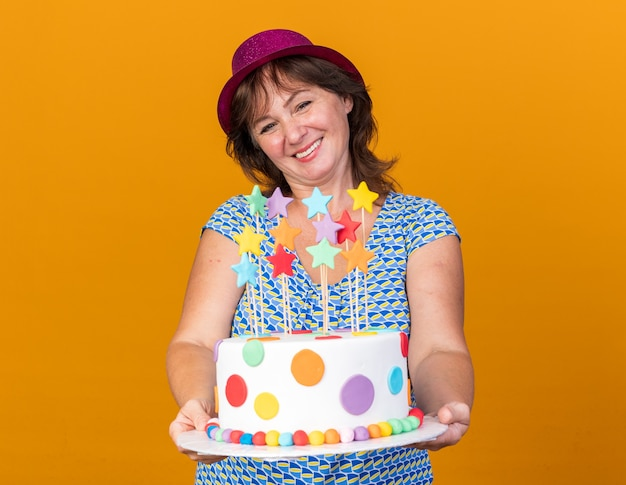 Middle age woman in party hat holding birthday cake  with smile on face happy and cheerful celebrating birthday party standing over orange wall