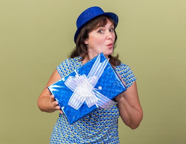 Donna di mezza età con cappello da festa che tiene un regalo di compleanno sorpreso festeggiando la festa di compleanno in piedi sopra il muro verde