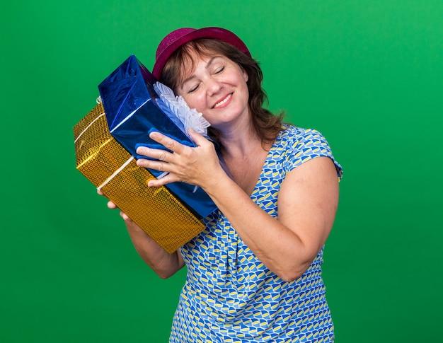 Donna di mezza età in cappello del partito che tiene i regali di compleanno sorridenti felici e positivi che celebrano la festa di compleanno che stanno sopra la parete verde