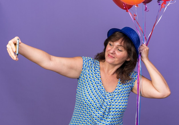 Donna di mezza età con cappello da festa che tiene un mazzo di palloncini colorati felice e allegra che fa selfie utilizzando lo smartphone che celebra la festa di compleanno in piedi sul muro viola