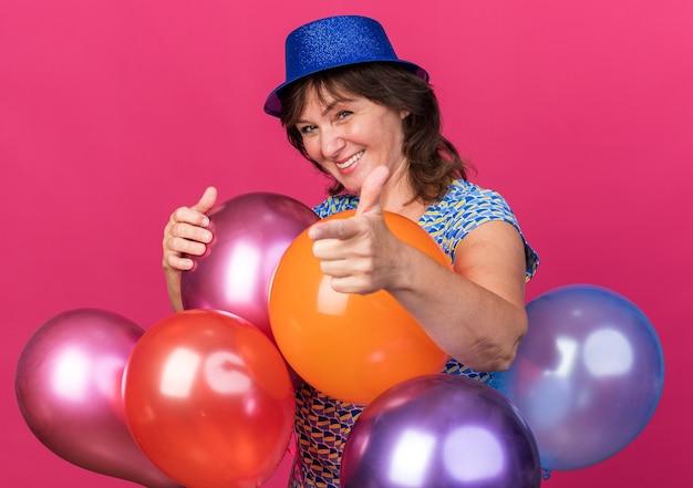 Donna di mezza età con cappello da festa che tiene palloncini colorati sorridendo allegramente puntando con il dito indice che celebra la festa di compleanno in piedi sul muro viola