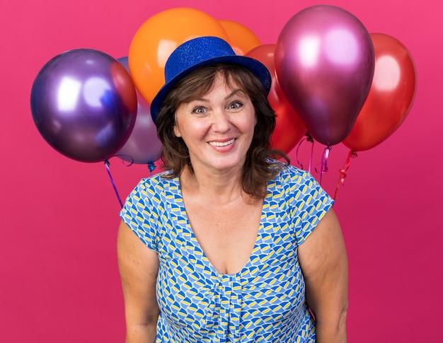 Donna di mezza età con cappello da festa che tiene palloncini colorati con faccia felice che sorride allegramente festeggiando la festa di compleanno in piedi sul muro rosa