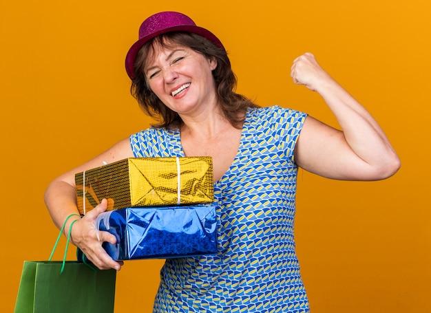 Donna di mezza età con cappello da festa che tiene in mano un sacchetto di carta con regali di compleanno felice ed eccitato che stringe il pugno