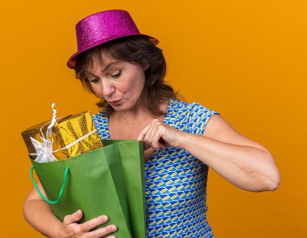 Donna di mezza età con cappello da festa che tiene in mano un sacchetto di carta con regali di compleanno che sembra incuriosita mentre celebra la festa di compleanno in piedi sul muro arancione orange