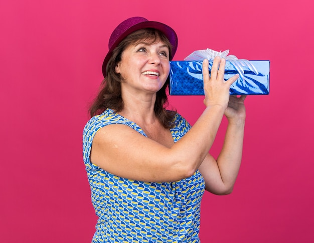 Donna di mezza età con cappello da festa che tiene in mano un regalo felice e allegro che sorride ampiamente