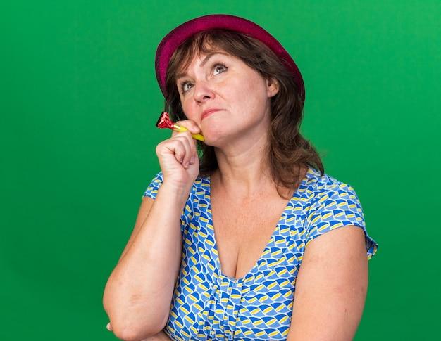 Donna di mezza età in cappello da festa con fischietto alzando lo sguardo perplesso che celebra la festa di compleanno in piedi sul muro verde