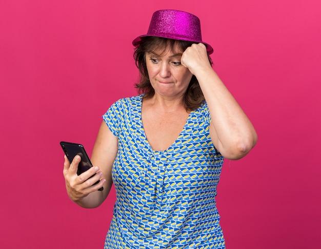 Donna di mezza età con cappello da festa che guarda lo schermo del suo smartphone confusa mentre celebra la festa di compleanno in piedi sul muro rosa