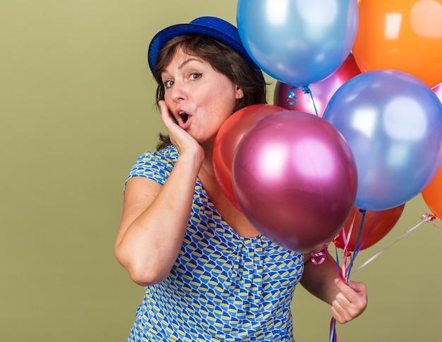 Donna di mezza età in cappello da festa con un mucchio di palloncini colorati sorpresa e felice che celebra la festa di compleanno in piedi sul muro verde green