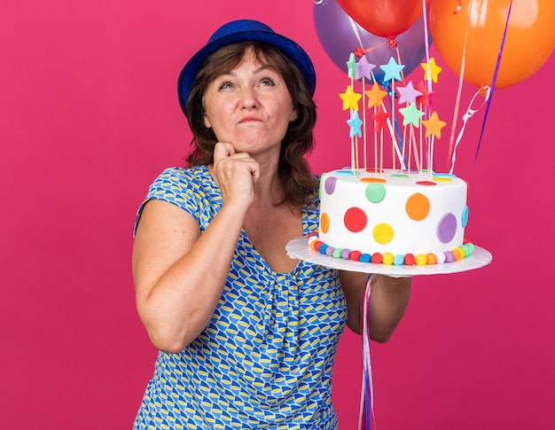 Middle age woman in party hat with colorful balloons holding birthday cake looking up with pensive expression thinking celebrating birthday party standing over pink wall