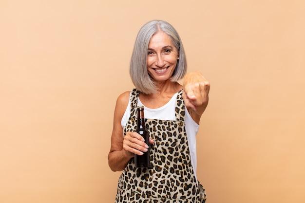 만족, 자신감, 친절한 미소로 카메라를 가리키는 중년 여성, 맥주와 함께 선택