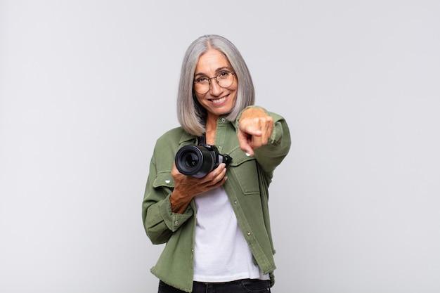 満足し、自信を持って孤立したカメラを指している中年女性