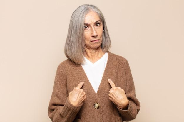 Женщина среднего возраста указывая на себя смущенным и насмешливым взглядом, потрясенная и удивленная тем, что ее выбрали