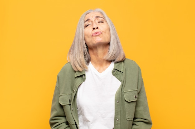 Middle age woman pressing lips together with a cute, fun, happy, lovely expression, sending a kiss