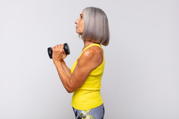 Middle age woman on profile view looking to copy space ahead, thinking, imagining or daydreaming. fitness concept