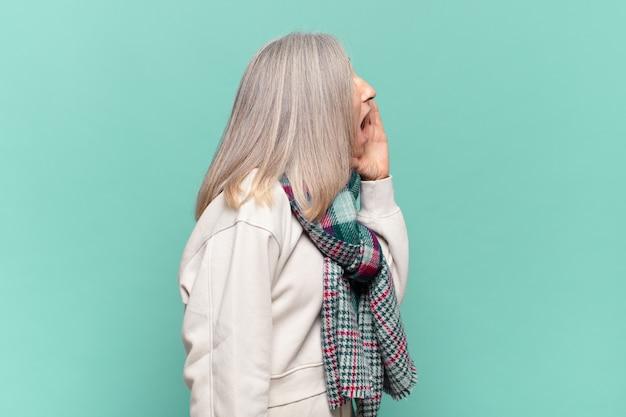 Вид профиля женщины среднего возраста, выглядит счастливой и взволнованной, кричит и зовет, чтобы скопировать пространство сбоку