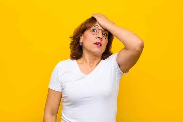 Middle age woman raising palm to forehead thinking oops, after making a stupid mistake or remembering, feeling dumb against yellow wall