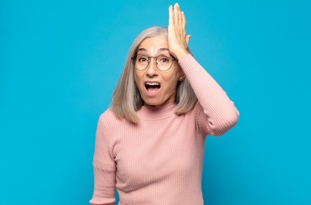 Middle age woman raising palm to forehead thinking oops, after making a stupid mistake or remembering, feeling dumb