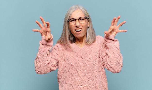 Женщина среднего возраста кричит от паники или гнева, шокирована, напугана или разъярена, положив руки на голову