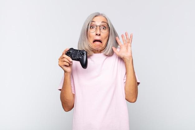 Женщина среднего возраста кричит с поднятыми руками, чувствуя ярость, разочарование, стресс и расстройство. концепция игровой консоли